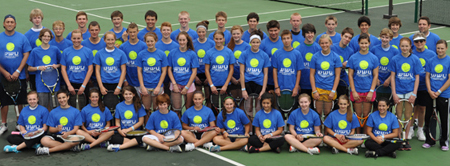 Tennis camp participants pose on the court