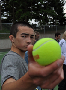 Teenager in a grey shirt holds up a tennis ball next to the camera