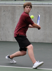 Teenage tennis player dressed in maroon and black winds up to hit a backhand shot