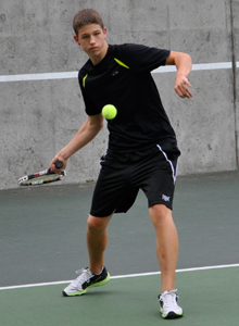 Teenage tennis player dressed in black winds up to hit the ball with a forehand shot