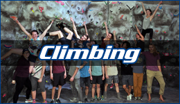 WWU Climbing team posing on the wall in the Wade King Rec Center with climbing written across