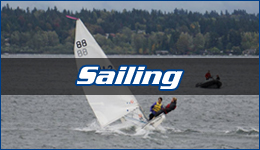 Sailing written across a white sailboat with 2 team members counterbalancing as it cuts through the water with a rubber zodiac trailing