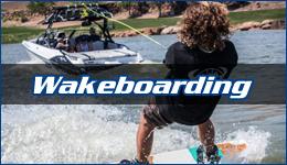 Wakeboarding written across a wakeboarder following a white boat near shore