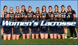 Women's lacrosse written across the team posed on the field