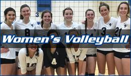 Women's Volleyball written across the team posing in front of a net