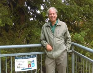 Tom Krabbenhoft stands next to railing, trees in background