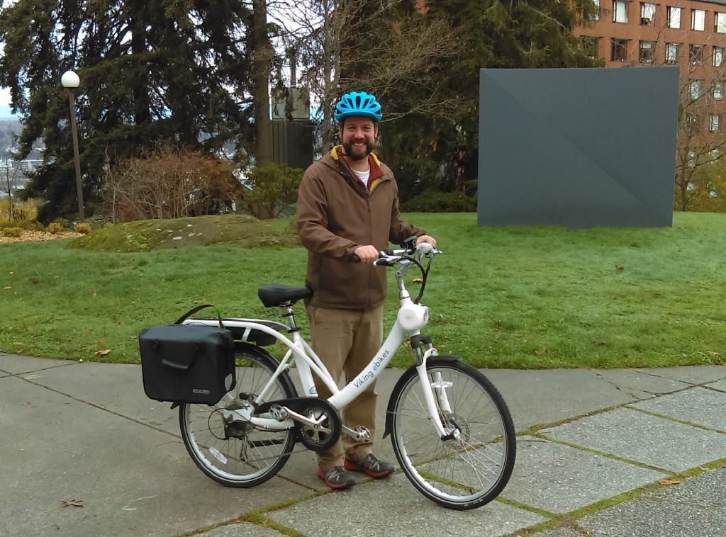 Tony Thompson stands behind bike, grassy area in background