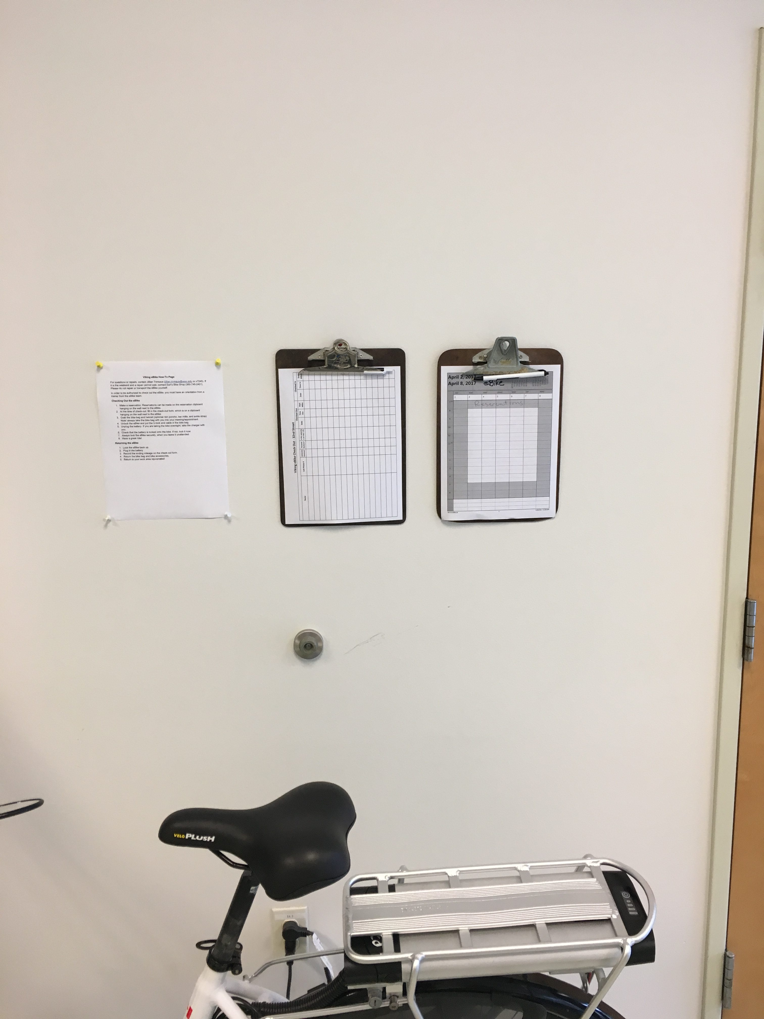 eBike up against a wall that's holding clipboards with paper