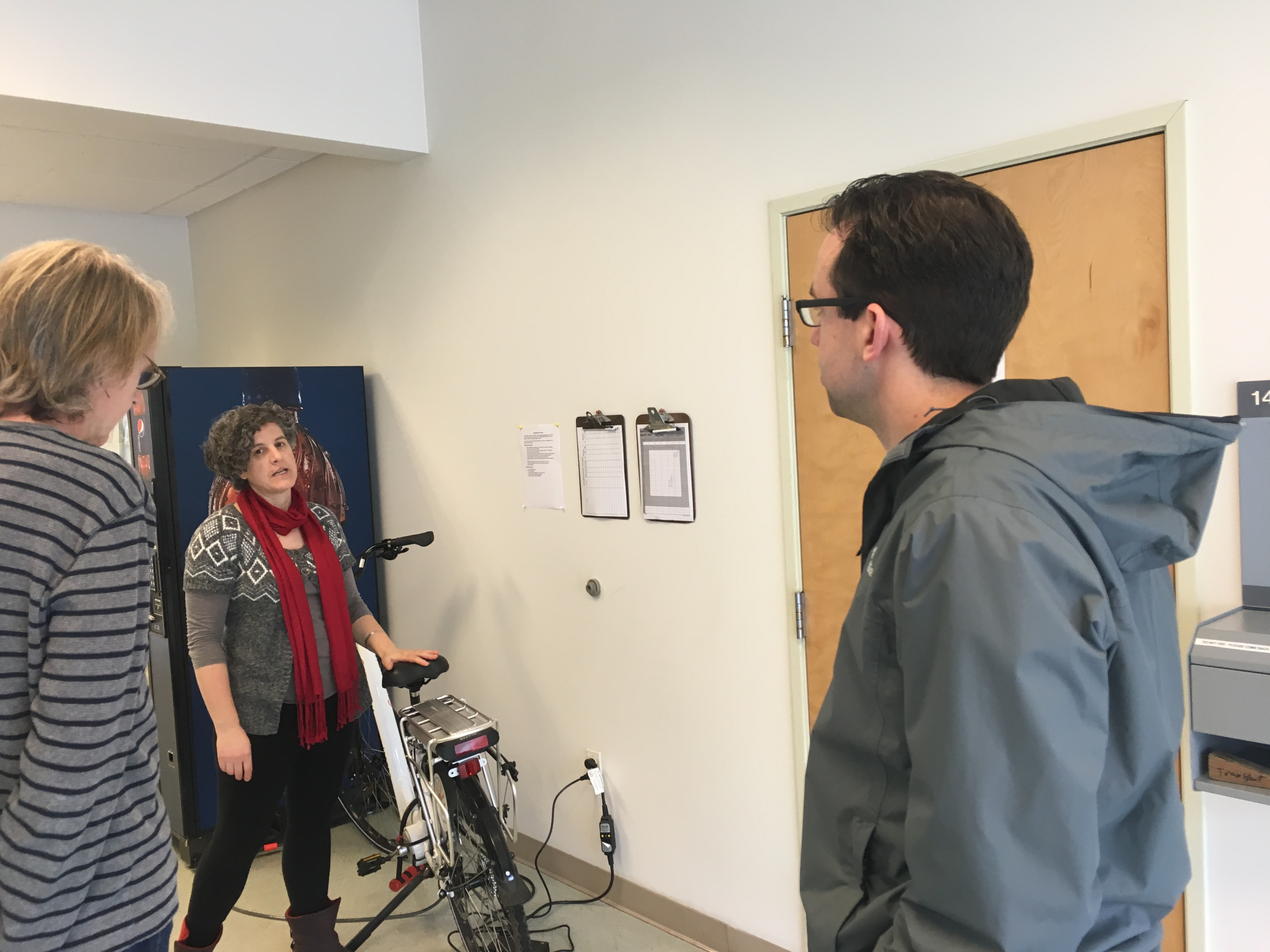 Woman stands next to bike, two other people face woman