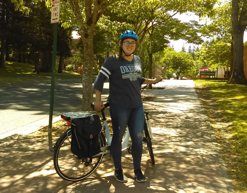 Woman in Oregon shirt stands in front of bike, trees in background