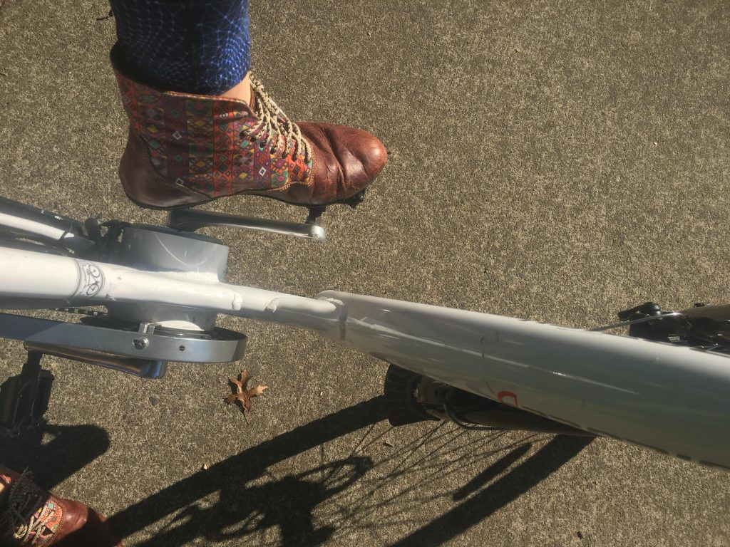Aerial shot of foot with brown patterned boot on bike pedal