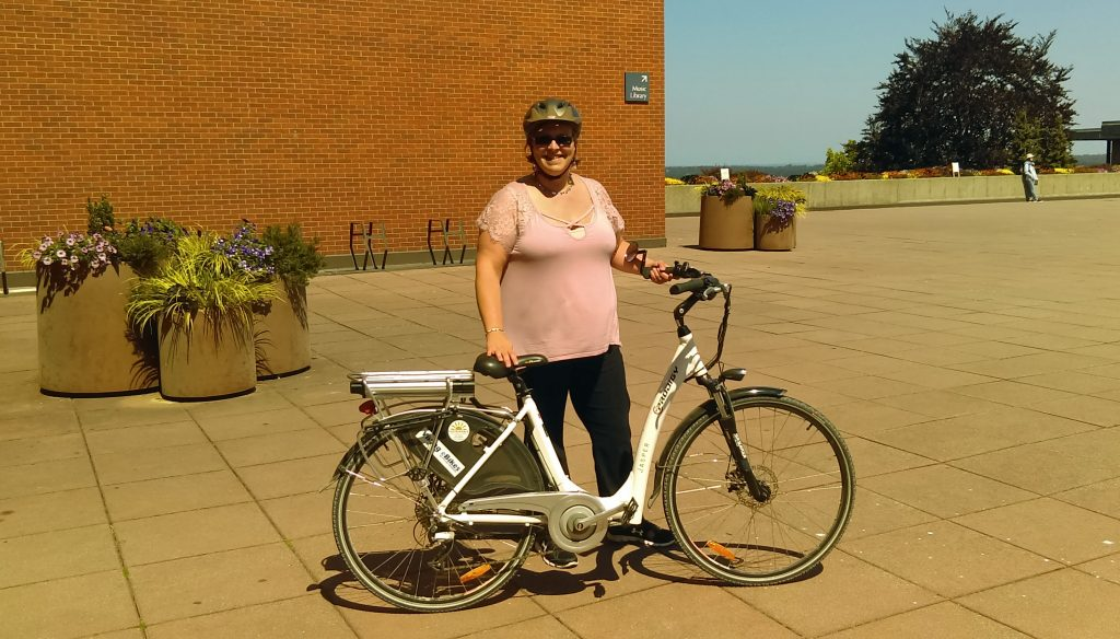 Stacey Maxwell standing outside of the Performing Arts Center on a sunny day, with her very own e-bike.