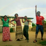 4 people dancing in front of double rainbow