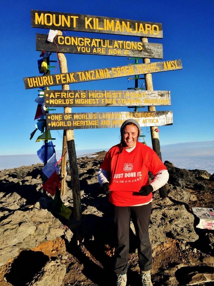 Smiling girl standing a sign marking the peak of Mount Kilmanjaro