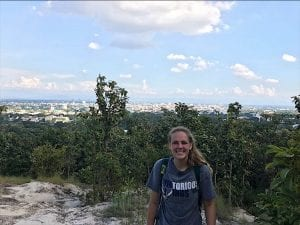 Student, with tree landscape in background