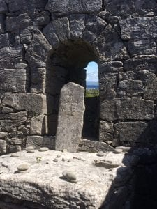 Stone with cross, in front of ancient stone wall with window