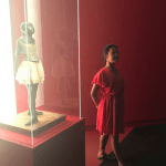 A student imitates the pose of a dancer statue in a display case