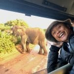 Student poses near an elephant