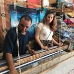 A man uses a loom to create woven fabrics