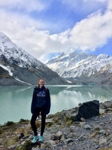Student posing in front of mountains and lake