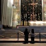 Two women kneel in front of a cross