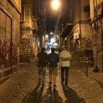 Three students walk down a graffiti-lined street