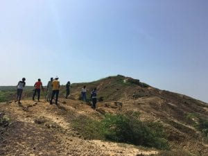 Visitors walk up a large hill
