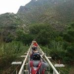 Students cross a narrow suspension bridge into a green mountain