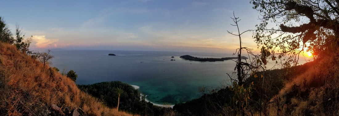 A view over the water of from the top of Adang Island at sunset.
