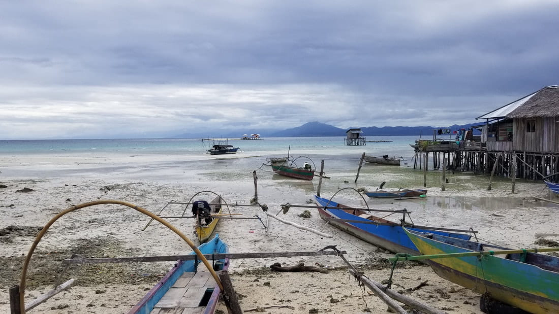 A view of small boats beached at the edge of the water in Sulawesi.