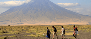 People walking in front of Tanzanian mountain
