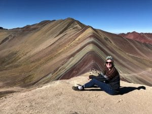 Honors student Jordan sits on a sunny hilltop in Peru
