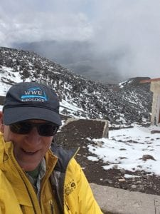 Dr. Linneman takes a selfie on a snowy mountaintop in Ecuador, showing off his 'WWU Geology' baseball cap.