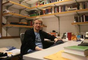 Dr. Goldman sitting in his office surrounded by shelves of books.