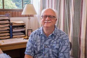 Dr. Moore sits at his desk in a blue Hawaiian shirt.