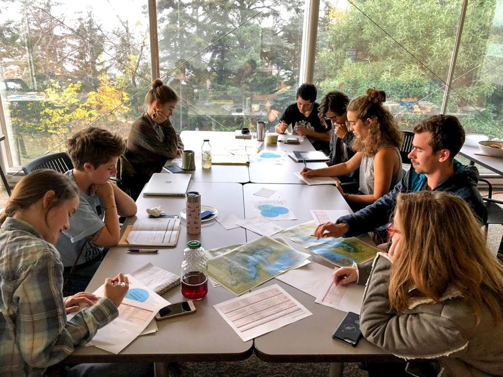 students in a classroom studying the map of the Salish Sea