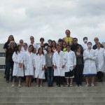 Group of students in lab coats and other gear on steps sculpture