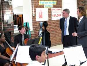 Superintendent Dr. Adams and music teacher Mr. McCarter talk with three orchestra members as they prepare to play for a board meeting.