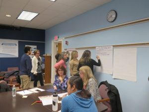 Nine members of the strategic planning committee working together to determine measurable objectives, during a meeting
