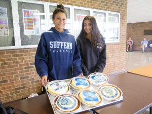 Two girls show off decorated cakes that say Suffern Central