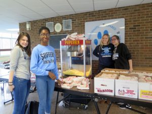 students serving popcorn