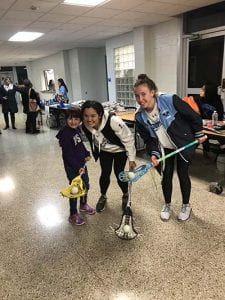 HS Lax players teach elementary student how to play the game