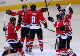 Chicago Blackhawks' Andrew Shaw, second from left, celebrates with teammates after scoring the winning goal in a third overtime against the Boston Bruins in Game 1 of the NHL Finals on June 12 at the United Center in Chicago.