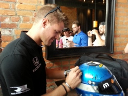 "James Jakes signs the helmet that ""Jakesy Nation"" designed for him, which he gave to the group at a media luncheon on May 21."