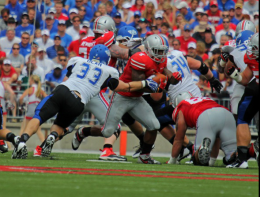 Shelby Lum / Photo editor Redshirt senior running back Jordan Hall pushes through the line with the ball in a game against Buffalo on Aug. 31. OSU won, 40-20