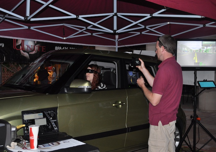 Marty Burke, a driving instructor with the Arrive Alive program, takes a photo of Megan Swanger, a third-year in nursing, while she does the Distracted Driving Simulator Sept. 26 outside of Ohio Union. Credit: Liz Young / Campus editor