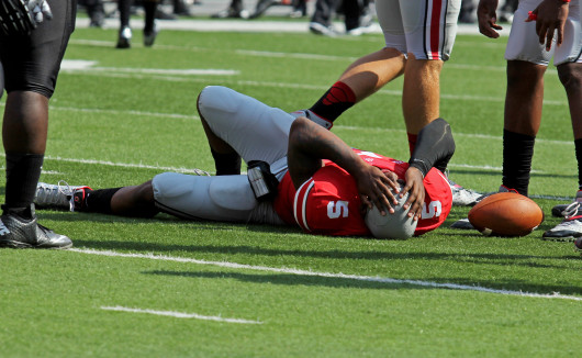 Ohio State junior quarterback Braxton Miller lies on the field in pain after injuring his knee in the first quarter against San Diego State. OSU won, 42-7. Shelby Lum / Photo editor