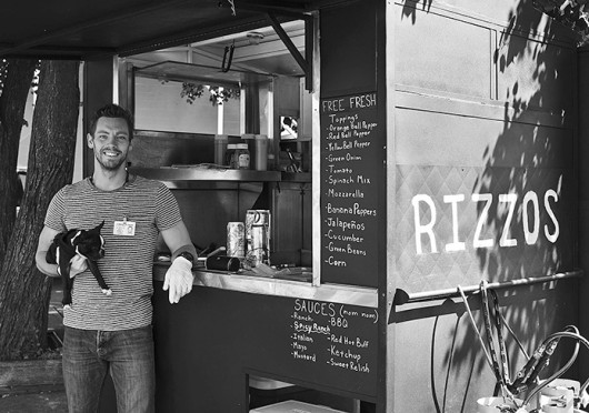 Ray Kinne, a 5th-year in photography, poses with his dog Rizzo in front of his food cart Rizzo's Eats, which is usually located on 14th Ave and High Street. Credit: Courtesy of Ken Snow