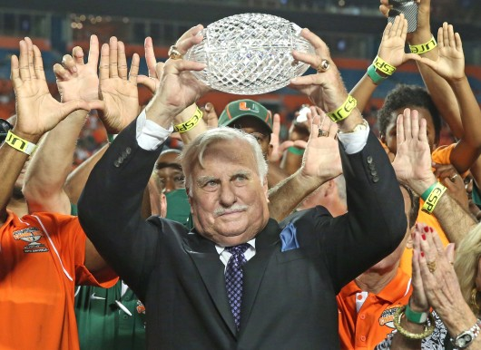 Former Miami coach Howard Schnellenberger raises the 1983 NCAA Championship trophy during halftime of a game against Florida Atlantic at Sun Life Stadium. Miami won, 34-6. Credit: Courtesy of MCT