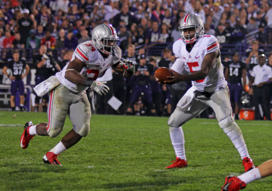 Junior quarterback Braxton Miller (5) hands off the ball to senior running back Carlos Hyde (34) during a game against Northwestern Oct. 5. OSU won, 40-30. Credit: Shelby Lum / Photo editor